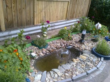 На фото водоем из старой ванной в саду